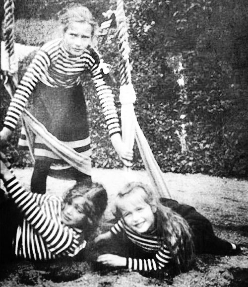 three of the sisters on a swing